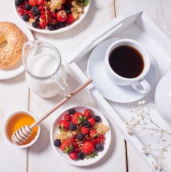Bayas dulces frescas en el plato blanco, bagel, taza de café y miel para el desayuno.