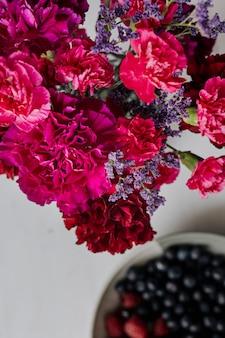 Bayas frescas y flores sobre la mesa