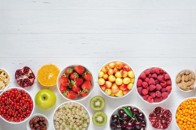 Bayas frescas, frutas, nueces en una madera blanca