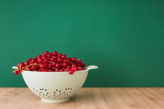 Bayas frescas de la grosella roja en el colador en el escritorio delante del fondo verde