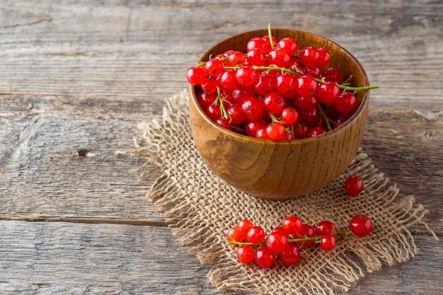 Bayas frescas de grosella roja en madera