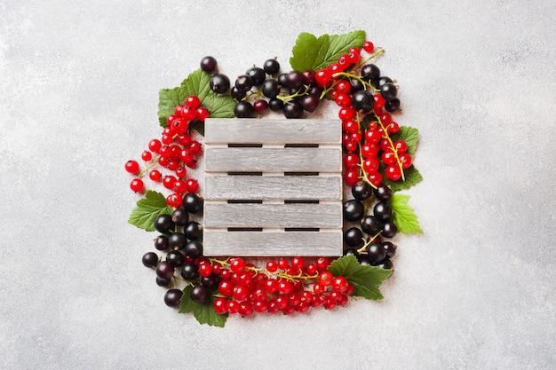 Bayas frescas de grosellas negras y rojas en la tabla gris con el espacio de la copia.