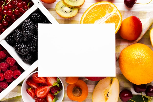 Bayas y frutas frescas y planas con papel.
