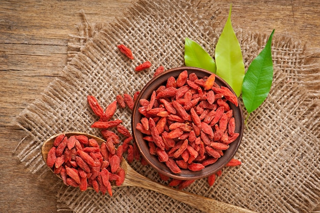 Bayas de goji secas rojas en cuchara de madera