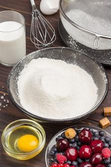 Bayas, harina tamizada en plato negro, cacao en polvo. taza de medir con harina, vaso de leche, huevo roto y sal, batidor de metal sobre la mesa.