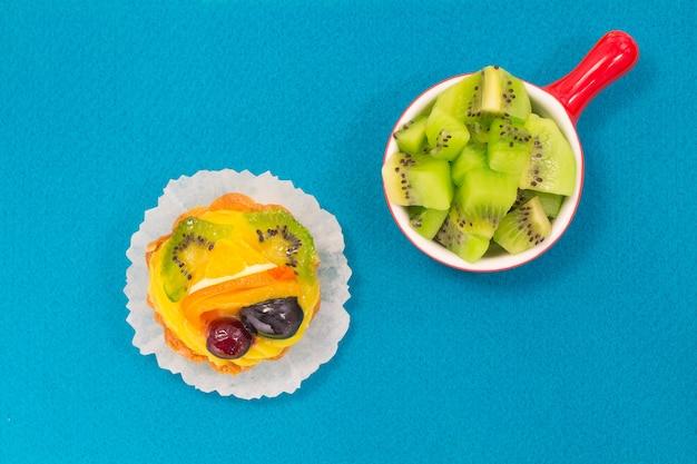 Bayas de kiwi verde en una placa roja. pastel con frutas sobre una superficie azul