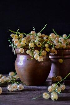 Bayas maduras de grosella dorada en frascos vintage metálicos. vista frontal