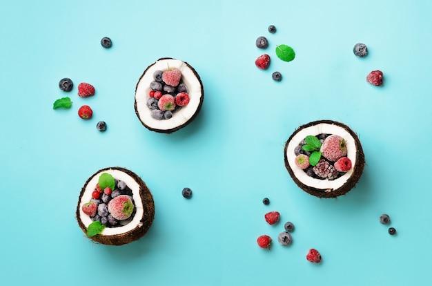 Bayas orgánicas frescas, hojas de menta dentro de cocos maduros. diseño de arte pop, concepto creativo de verano. la mitad de coco en estilo minimalista.