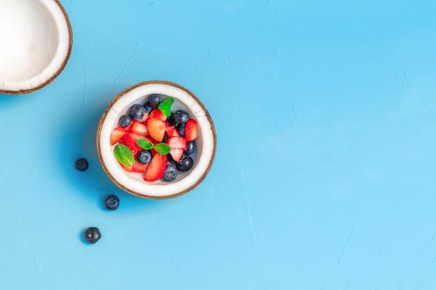 Bayas orgánicas frescas en un tazón de coco en la mesa de color azul claro. concepto de alimentación orgánica saludable