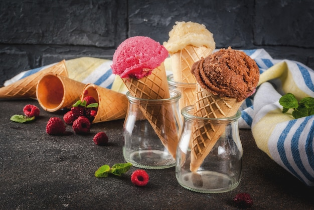 Bayas y postres dulces de verano, varios de sabor helado en conos de color rosa