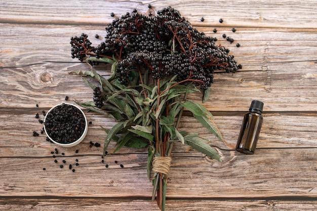 Bayas de saúco negro europeo y aceite de esencia sobre una superficie de madera