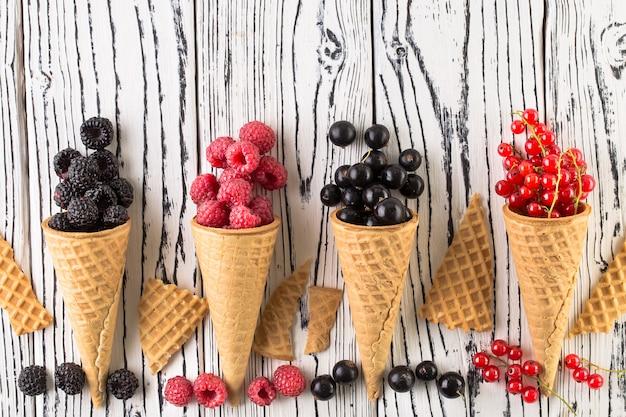 Bayas de verano en cono de waffle sobre fondo blanco de madera