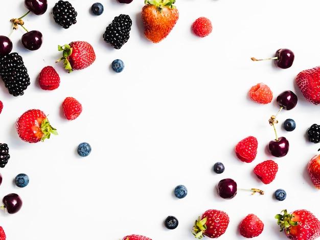 Bayas de verano deliciosas en superficie blanca