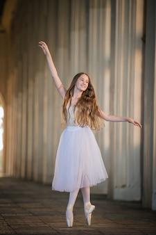 Bayerina joven con una falda larga blanca con cabello largo suelto se encuentra en una elegante pose en pointes