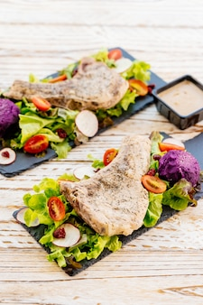 Bbq a la parrilla chuleta de cerdo carne filete en plato negro con vegetales