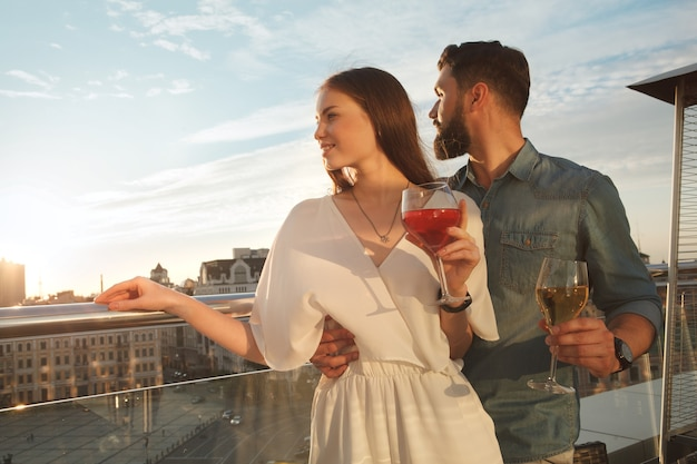 Beautidul elegante pareja mirando las vistas de la ciudad desde la terraza del restaurante, espacio de copia