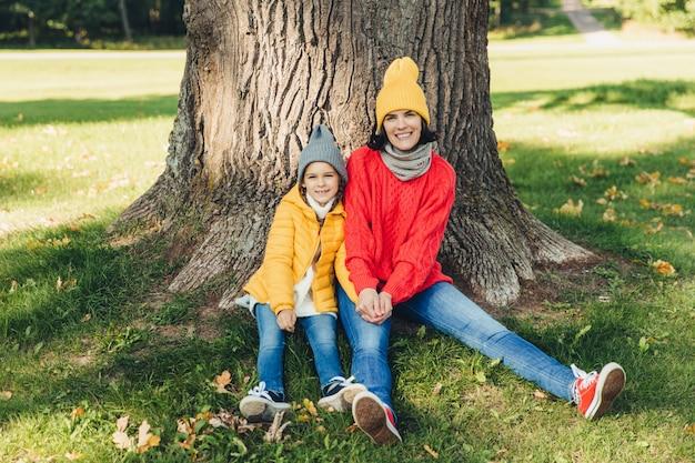 Beautiul hembra lleva gorro de punto y swetaer se sienta junto a su pequeña hija cerca del árbol