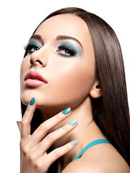 Beautiul moda mujer con uñas y maquillaje turquesa - en la pared blanca
