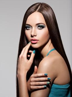 Beautiul mujer elegante con maquillaje turquesa y pelos largos - posando