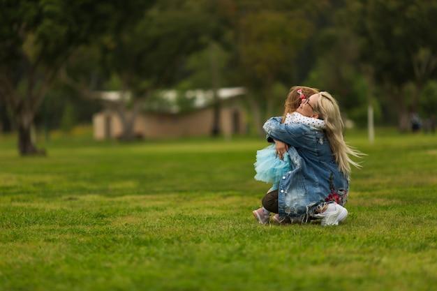 Bebé abrazando con mamá en el parque en la hierba verde