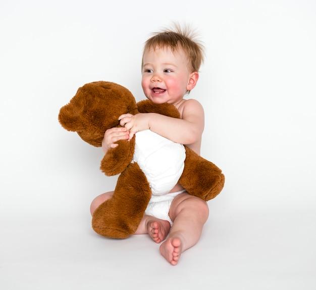 Bebé abrazando a su osito de peluche
