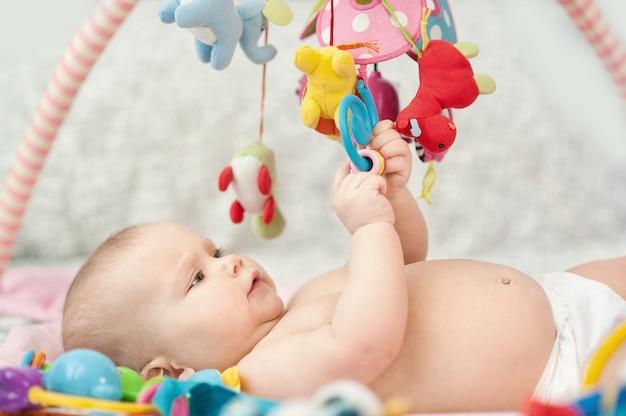 Bebé acostado en el desarrollo de la alfombra. jugando en el móvil. juguetes educativos. dulce niño gateando y jugando con juguetes en la alfombra