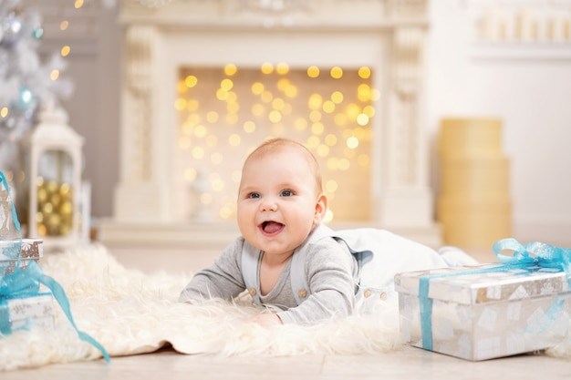 El bebé está acostado sobre una alfombra mullida con cajas de regalo.