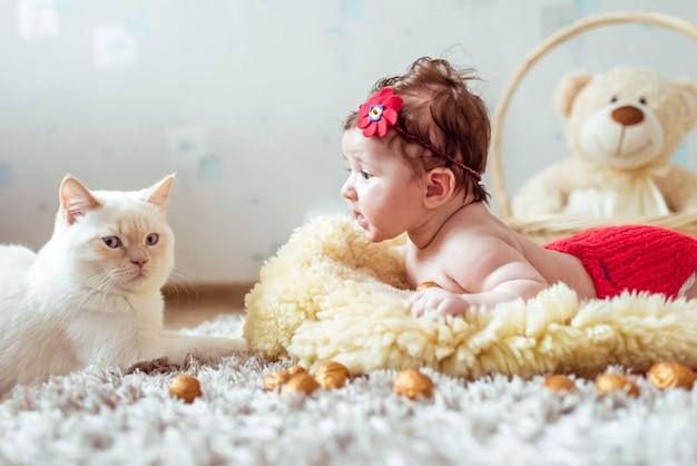 Bebé acostado sobre una manta y mirando a un gato