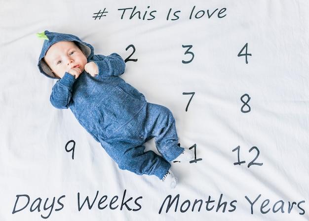 Bebé adorable con pijama de dinosaurio sobre calendario