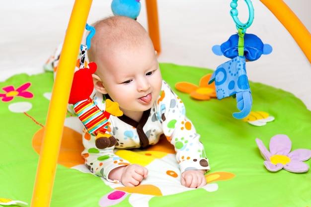 Bebé adorable que se divierte con los juguetes en la estera colorida del juego.
