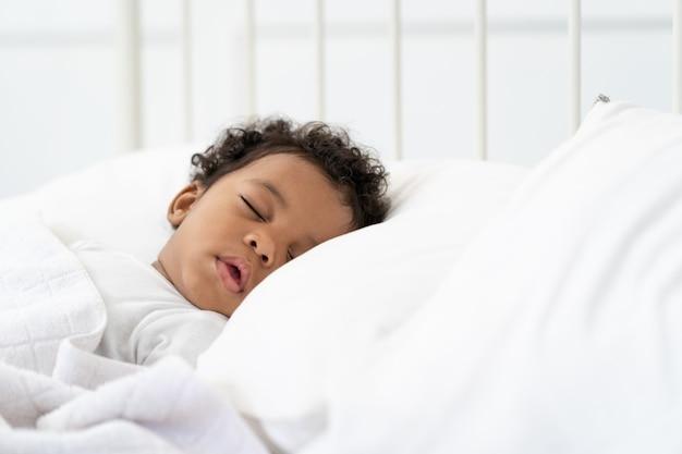 Bebé afroamericano negro durmiendo en un colchón blanco.