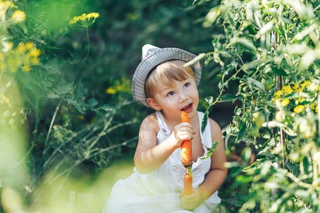 Bebé agricultor con zanahorias y ropa cacual sentado en la hierba verde