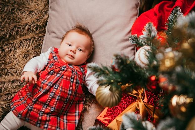 Bebé al lado del árbol de navidad