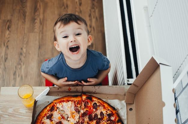 Bebé al lado de una gran pizza en la cocina, muy sorprendido por el tamaño.