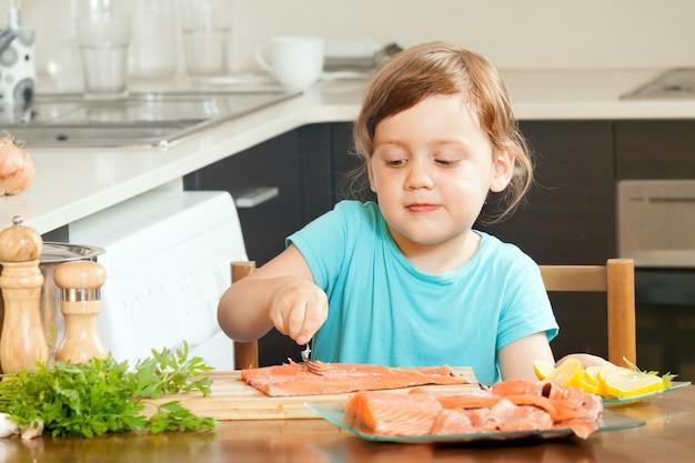 Bebé ama de casa cocinar salmón Foto gratis