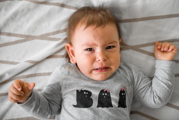 Bebé de un año llorando en la cama.