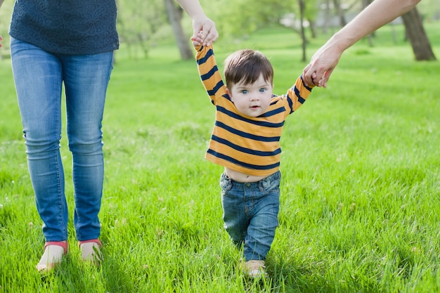 Bebé aprendiendo a caminar con la ayuda de las manos de madres y padres