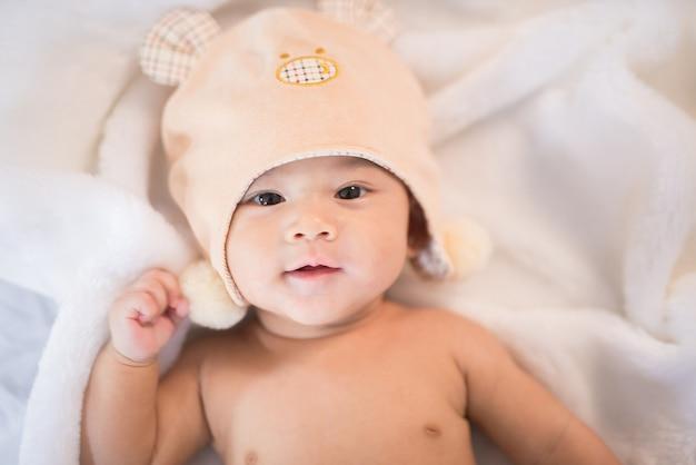 Bebé de asia del retrato en la cama blanca