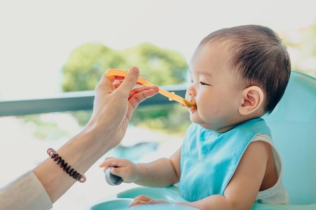 Bebé asiático de 7 meses comiendo comida mezclada en una silla alta