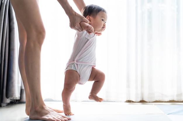 Bebé asiático dando los primeros pasos camina hacia adelante sobre la alfombra suave con la ayuda de la madre en casa.