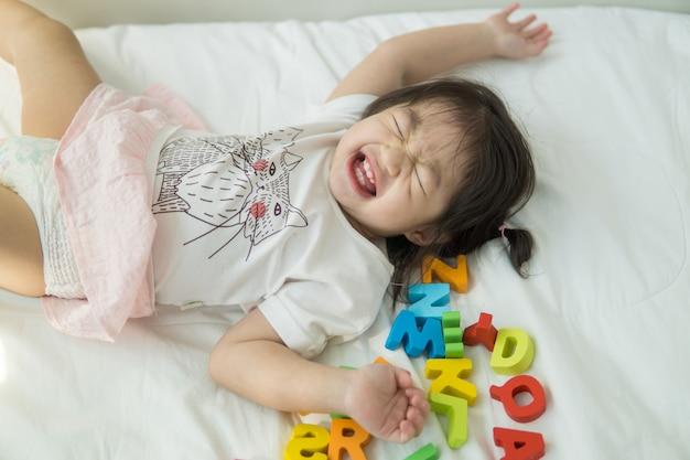 Bebé asiático jugando letras abc en una cama