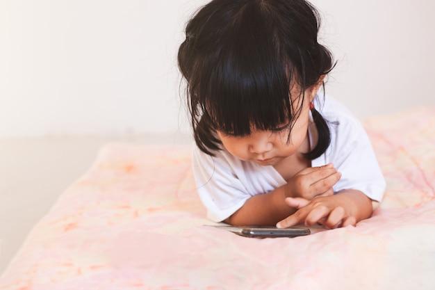 Bebé asiático lindo que juega el smartphone que miente en su cama en su sitio