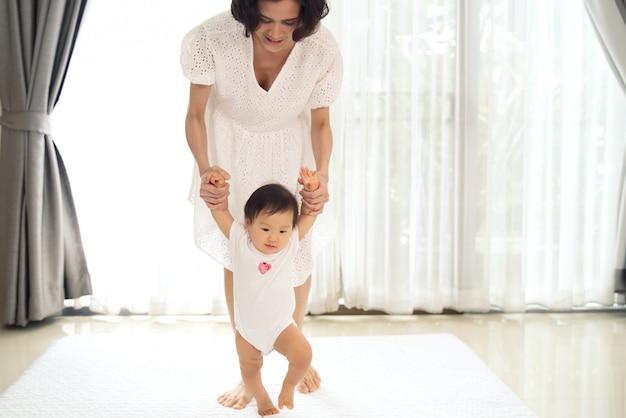 El bebé asiático que da los primeros pasos camina hacia adelante con la ayuda de la madre.