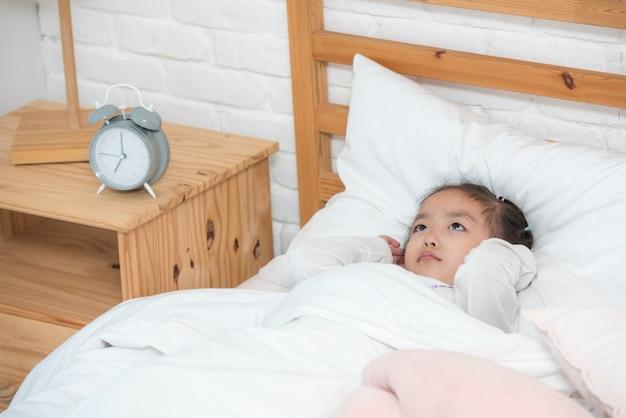 Bebé asiático que despierta en cama con la muñeca infeliz.