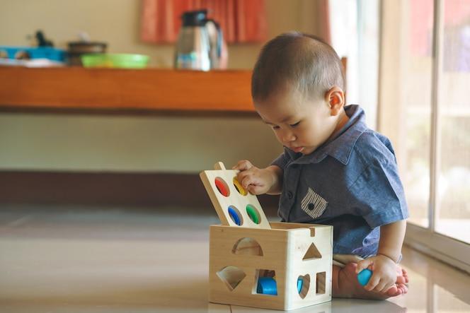 Bebé asiático que juega la caja de juguetes de madera