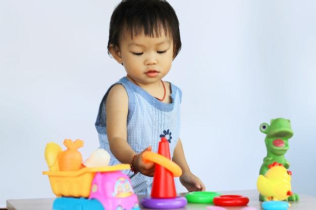 Bebé asiático que juega con muchos juguetes.