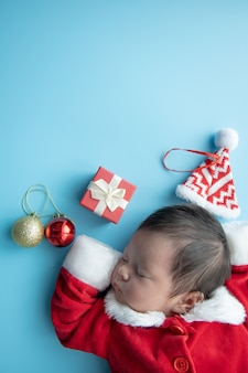 Bebé asiático recién nacido en uniforme de papá noel durmiendo con caja roja presente y sombrero rojo sobre fondo azul.