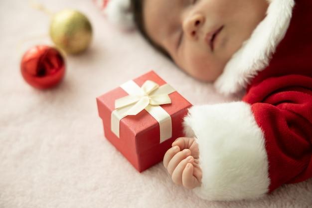 Bebé asiático recién nacido en uniforme de papá noel durmiendo con caja roja presente y sombrero rojo