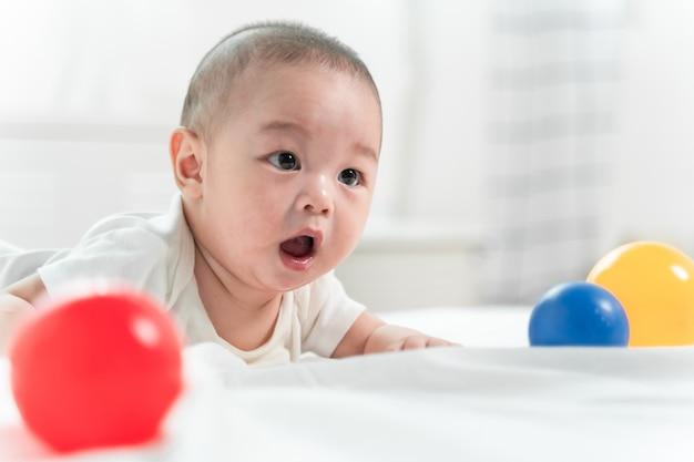 Bebé asiático está riendo y jugando a la pelota de juguete en la cama blanca con sentirse feliz y alegre