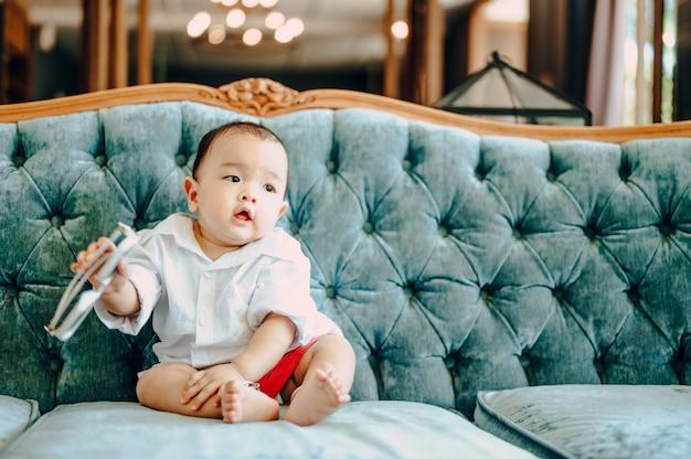 Bebé asiático sentado en el sofá, concepto de moda de verano